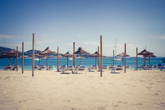 Beach loungers and umbrellas on the beach Stock Images