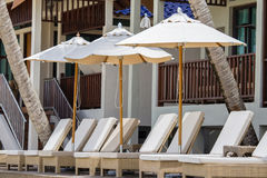 Beach loungers and umbrellas on the beach next to the sea in tropical hotel. Thailand Royalty Free Stock Photography