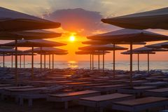 Beach loungers and umbrellas on a deserted beach in the evening. Silhuettes of beach loungers and umbrellas on a deserted beach in the evening on a sunset royalty free stock photo