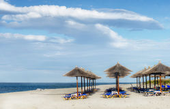 Beach, Loungers and Umbrellas. Beach loungers and umbrellas on white sand beach Royalty Free Stock Photos