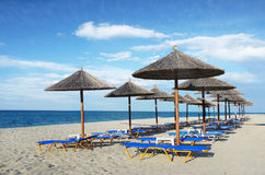 Beach, Loungers and Umbrellas. Beach loungers and umbrellas on white sand beach Stock Photos