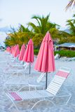 Beach lounges under an umbrella on white sand Royalty Free Stock Photo