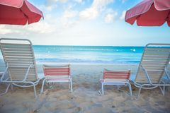 Beach lounges under an umbrella on white sand Stock Photos
