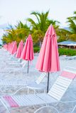 Beach lounges under an umbrella on white sand Stock Photography