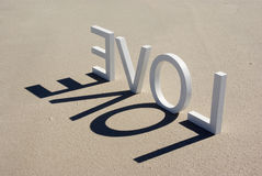 Beach Love 2. Block letters spelling out the word love and casting shadows of the word on beach sand stock image