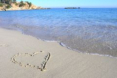 Beach love heart. Love heart in the sand on beach with clear sea Stock Images