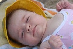 BEach Lovin'. 2 month old baby girl lying on a towel in the sand, at the beach (NJ SHORE Royalty Free Stock Image