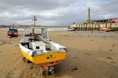 The beach at low tide with mooring boats and Margate Harbor Arm on the right side, Margate, Kent, UK. The beach at low tide with mooring boats and Margate Harbor Royalty Free Stock Photos
