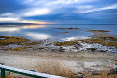Beach and low tide on Penobscot Bay. View of a beach with a handrail in the foreground and stormy skies above at dawn at Penobscot Bay in Searsport, Maine Stock Photos