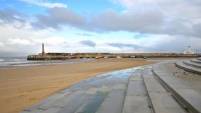 The beach at low tide by stormy and windy weather with Margate Harbor Arm in the background, Margate, Kent, UK. The beach at low tide by stormy and windy weather Royalty Free Stock Photography