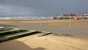 The beach at low tide by stormy and windy weather with Margate Harbor Arm in the background, Margate, Kent, UK. The beach at low tide by stormy and windy weather Royalty Free Stock Photo