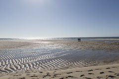 Beach on low tide with two strollers. Lonely Beach during low tide, 2 people walking on the edge Royalty Free Stock Image