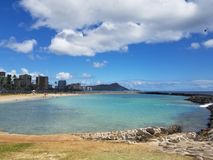 Beach on Magic Island in Ala Moana Beach Park. On the island of Oahu, Hawaii.  Waikiki and Diamond Head in the distance and helicopter in the air on a beautiful Stock Photography