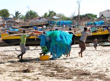 Beach with Malagasy canoes and fishermen with fishing nets, Madagascar Royalty Free Stock Images