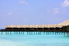 A beach in the Maldives with bungalows. Beach, ocean, turquoise water and a serie of bengalows in the Maldives Royalty Free Stock Photo