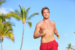 Beach man running smiling happy in swimwear. On tropical summer beach with palm trees. Handsome good looking muscular male model or lifeguard jogging training Royalty Free Stock Photography
