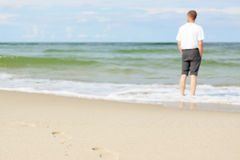 Beach man standing water back view shallow dof footprints Royalty Free Stock Photos