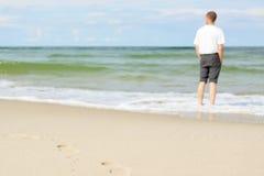 Beach man standing water back view shallow dof footprints. Sand Royalty Free Stock Photos