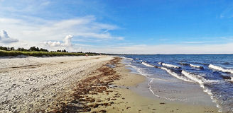 Beach in Marielyst, Denmark - baltic sea. Beach in Marielyst, denmark with ocean waves of baltic sea and blue sky - panorama view Royalty Free Stock Image
