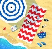 Beach mat and parasol near sea surf Stock Photo