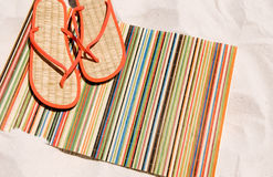 Beach mat and shoes on sand Royalty Free Stock Images