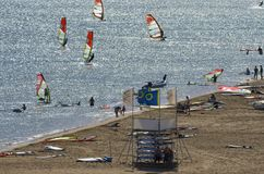Summer beach on the Mediterranean sea with the tourists and the windsurfers stock photography