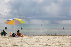Beach of Miami and showers on the sea. Miami Beach, Florida, USA - August 2015: some people enjoy the beach while, far over the sea, some showers threaten the Stock Image