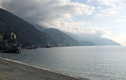 The beach at Monterosso al mare. Water, mountains and storm cloud Stock Photos