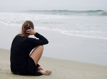 Beach Mood. Beatiful woman sitting pensively pondering on the beach shore in the early morning fog Royalty Free Stock Image