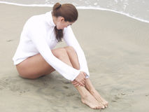 Beach Mood 602. Beatiful woman sitting on the wet sand on the seashore in the early morning fog wearing a white turtle-neck sweater and looking down at the sand Royalty Free Stock Photography