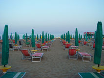 Beach in the morning, empty lounge chairs and sunshades of bright color, neatly placed Royalty Free Stock Photo