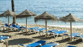 Beach morning scenery with sunbeds and umbrellas in front of the sea Stock Photos