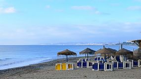 Beach morning scenery with umbrellas and sunbeds Royalty Free Stock Photo
