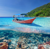Beach and motor boat with coral reef underwater view. Beautiful beach and motor boat with coral reef bottom underwater and above water split view Stock Image