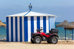 Beach Motorbike in front of a Hut. A red four-wheeled beach vehicle in front of a hut on a sandy beach Stock Photo