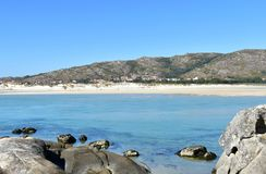 Beach with mountain. White sand and clear water with rocks and turquoise colour. Small coastal village, Galicia, Spain. Sunny day. Galicia, La Coruna Province royalty free stock photos