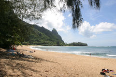 Beach and mountains on Kauai. White clouds in a blue sky over mountains and sandy beach on Kauai island, Hawaii stock images