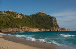 Beach near green mountains. Sand beach, azure sea and green rocks in background Stock Image
