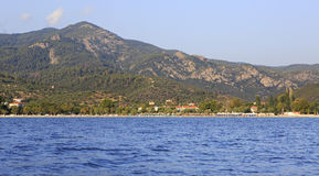 Beach in Neos Marmaras and mountains of Sithonia. Royalty Free Stock Images
