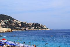 Beach in Nice. People swim in the sea or enjoy the sunshine on the beach. The sea and the sky are blue Stock Photo