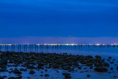 Beach at night. With city skyline lit up with an old jetty Stock Photos