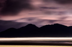 Beach at night with sand, sea waves and mountains. Beach at night with sand, sea waves and silhouette of mountains in the background. Long exposure photo royalty free stock image