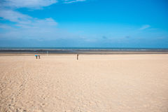 Beach of the North Sea in Koksijde, Belgium under blue sky.  Stock Image