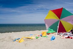Beach objects. Sun umbrella, plastic buckets and spades scattered in the sand on the beach Royalty Free Stock Photography
