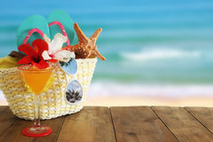 Beach objects and fruit cocktail on wooden table in front of sea landscape background royalty free stock image