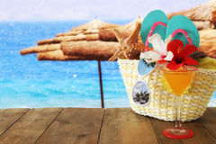 Beach objects and fruit cocktail on wooden table in front of sea landscape background stock image