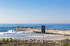 Beach Ocean and Concrete Mier with many Fisherman Stock Photo