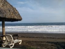 Sand and the ocean with hut and chairs stock photography