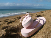 Beach, Ocean, Sky. View of flip flops on a yellow sand beach against ocean with island and blue sky background stock images