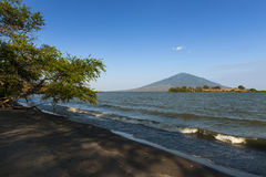 Beach in the Ometepe Island in Lake Nicaragua, with a volcano on the background, in Nicaragua Stock Photo